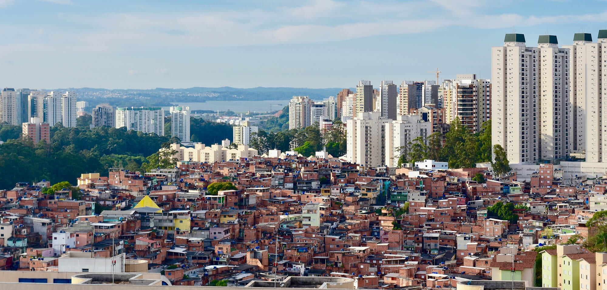 Favela slum with high-rises and lake in background in Sao Paulo